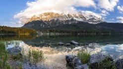 Alemania, Baviera, Grainau, montañas de Wetterstein, lago Eibsee con Zugspitze durante el día - foto de stock
