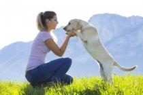 Woman with Labrador Retriever on Alpine meadow — Stock Photo