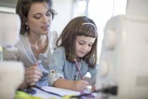 Mother and daughter designing clothes at home — Stock Photo