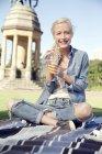 Giovane donna in parco con soft drink — Foto stock