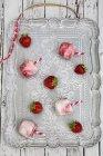 Vista superiore di quattro porzioni di gelato fragola latticello con bere cannucce e fragole fresche sulla zolla — Foto stock