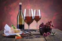 Still life with wine bottle, wine glasses, cheese and grapes — Stock Photo