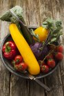 Bowl of fresh vegetables on wooden table — Stock Photo