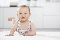 Ritratto ravvicinato della bambina sdraiata sul tappeto — Foto stock