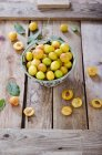 Mirabelles in a bowl on a wooden tray — Stock Photo