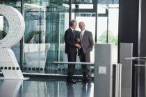 Zwei Geschäftsleute sprechen im modernen Büro — Stockfoto
