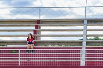 American High School Girl en tenue de sport assis tout seul sur les gradins du stade — Photo de stock