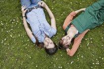 Jovens mulheres deitadas na grama, sorrindo — Fotografia de Stock