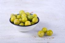 Prugne mirabelle in ciotola sulla tavola di legno bianco — Foto stock