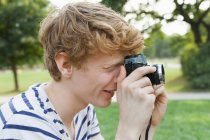 Young man taking a picture in park with an old-fashioned camera — Stock Photo