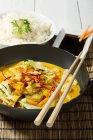 Frango picante com curry vermelho, pimentas, pimentões, cenouras, leite de coco e tigela de arroz na esteira de tabela — Fotografia de Stock