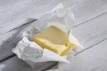 Pedaço de manteiga fresca em papel — Fotografia de Stock