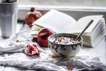 Healthy breakfast with pomegranate in yogurt, coffee and opened book — Stock Photo