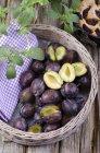 Cesto di prugne fresche sulla tavola di legno rurale — Foto stock