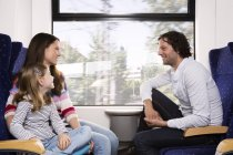 Family traveling in train, smiling sitting by the window — Stock Photo