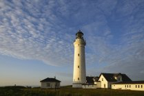 Denmark, North Jutland, lighthouse and buildings with cloudy sky on background — Stock Photo