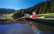 Woman with children rowing in boat in lake of Altenmarkt-Zauchensee, Austria — Stock Photo