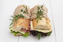 Baguette sandwiches with rosemary on white wood — Stock Photo