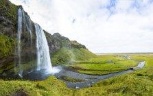 Islande, Sudurland, Paysage pittoresque avec prairie verte et vue sur la cascade de sejalandsfloss — Photo de stock