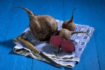 Halved and whole beetroots on cloth and knife on blue wooden table — Stock Photo