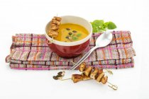 Elevated view of creamed pumpkin soup in bowl with chicken skewers on white background — Stock Photo