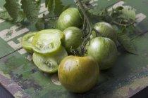 Pomodori tagliati a metà e tutta verde zebra su legno verde — Foto stock