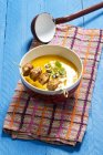 Elevated view of creamed pumpkin soup in bowl with chicken skewer on blue wooden table — Stock Photo