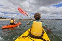 Portugal, Lagos, Teenage boy and mature woman rowing Kayak — Stock Photo