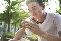 Hamburger de jeune homme manger à l'extérieur — Photo de stock