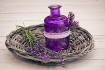 Лавандовые цветы с корзиной и бутылкой на деревянном столе, крупным планом — стоковое фото