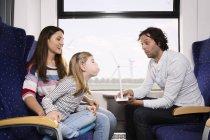 Семья путешествует в поезде, девушка дует на модели ветряной турбины — стоковое фото