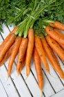 Freschi mazzi di carote con gambi su legno bianco — Foto stock