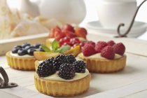 Mini pies with vanilla pudding and various fruits on wooden tray — Stock Photo