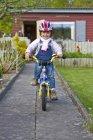 Girl riding bicycle at backyard — Stock Photo