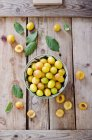 Fresh Mirabelle plums in bowl on wooden tray — Stock Photo