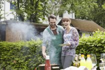 Young couple at barbecue, smiling — Stock Photo