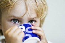 Портрет блондинка маленькая девочка, пить из синего и белого узорной Кубок — стоковое фото
