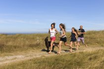 Parents and daughters running with dog on coast — Stock Photo