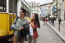 Portugal, Lisboa, Baixa, Rossio, young couple with city map in front of tram — Stock Photo