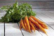 Букет з органічних морква з стебла на сірий дерев'яний стіл — стокове фото