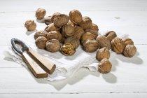 Noci con Schiaccianoci e piatto tovagliolo sulla tavola di legno bianca — Foto stock