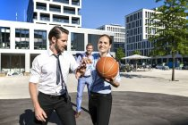 Group of businesspeople playing basketball outdoors — Stock Photo