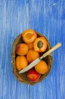 Fresh whole and halved Apricots in basket with knife on blue wood — Stock Photo