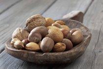 Pelle en bois avec mélange de noix sur la surface en bois — Photo de stock