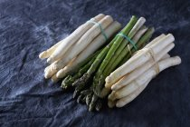 Bouquets d'asperges vertes et blanches sur textile noir — Photo de stock