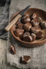 Chestnuts in wooden bowl with knife on sackcloth — Stock Photo