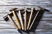 Old used hammers on wooden surface — Stock Photo