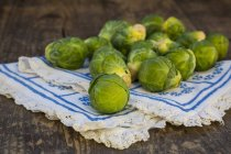 Brussels sprouts on dark wooden table with fabric — Stock Photo