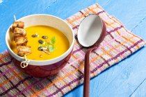 Close-up of creamed pumpkin soup in bowl with chicken skewer on blue wooden table — Stock Photo