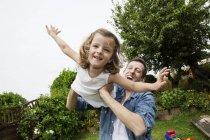 Отец играет со своей маленькой дочерью в саду — стоковое фото